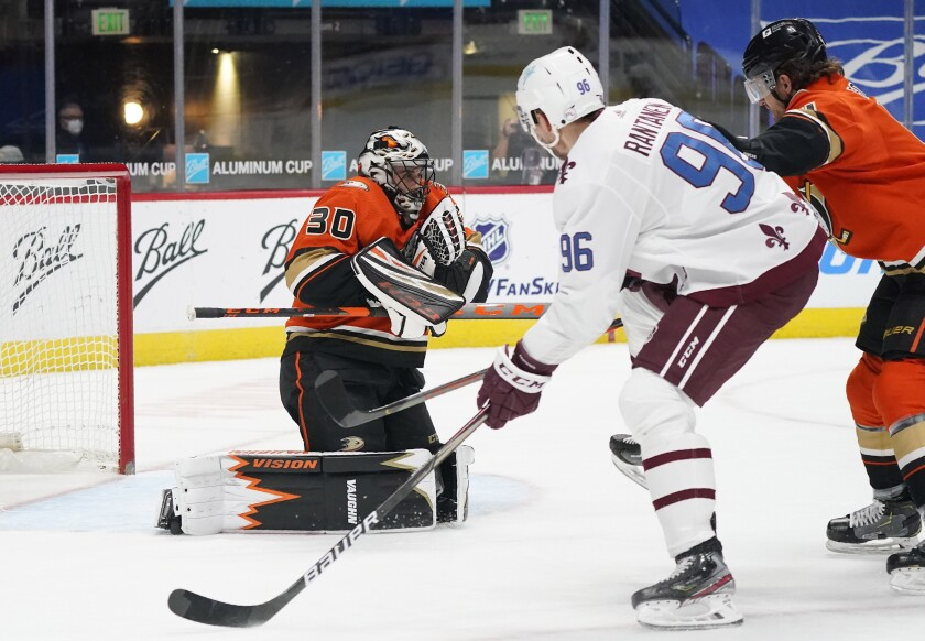 Anaheim Ducks goaltender Ryan Miller, left, stops a shot by Colorado Avalanche right wing Valeri Nichushkin, center, as Ducks' Hampus Lindholm defends during the first period of an NHL hockey game Saturday, March 6, 2021, in Denver. (AP Photo/David Zalubowski)