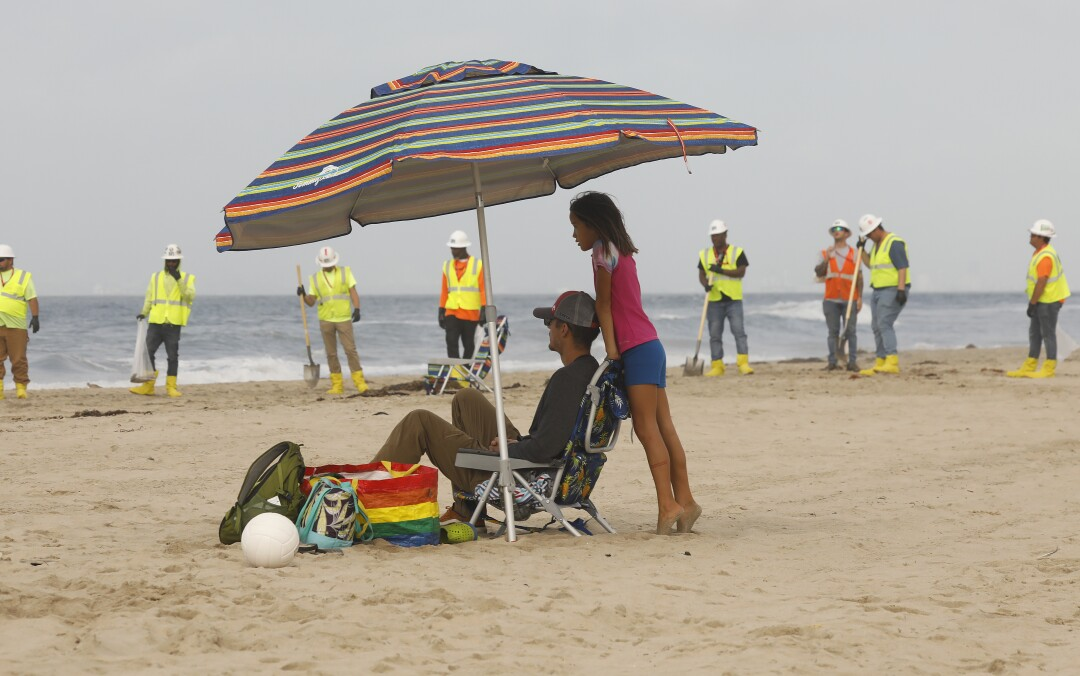 People sit on the beach with a cleanup crew in the background