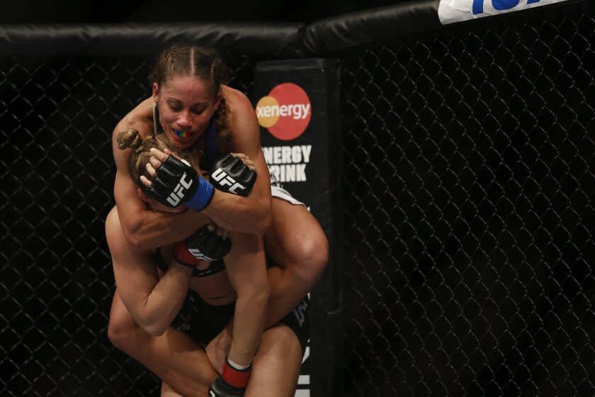 Ronda Rousey, in black, faces Liz Carmouche during the main event of UFC 157 at t he Honda Center in Anaheim.  Rousey successfully defended her UFC women's bantamweight championship with a first round armbar submission.