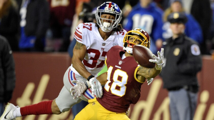 Redskins wide receiver Josh Doctson attempts a one-handed catch while defended by Giants defensive back Ross Cockrell during the first half Thursday night.