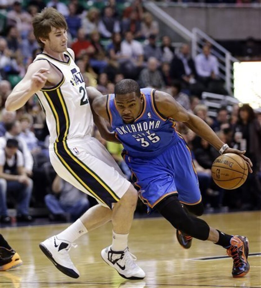 Oklahoma City Thunder's Kevin Durant (35) drives around Utah Jazz's Gordon Hayward, left, in the first quarter during an NBA basketball game, Tuesday, April 9, 2013, in Salt Lake City. (AP Photo/Rick Bowmer)