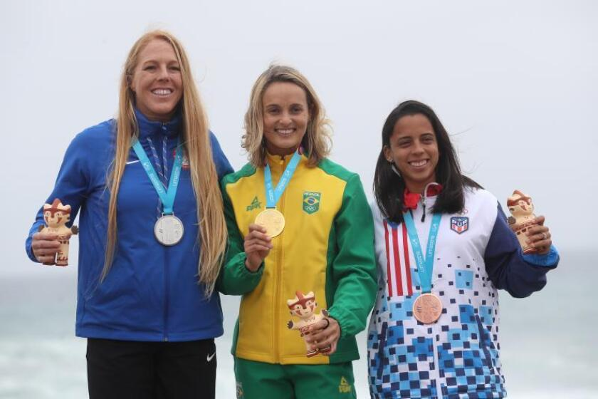 Lena Guimaraes (c) de Brasil, medalla de oro, posa junto a Candice Appleby (i) de Estados Unidos, plata, y Mariecarmen Rivera de Puerto Rico, bronce, este domingo en la premiación de surf carrera SUP femenino en los Juegos Panamericanos Lima 2019, en Lima (Perú). EFE/Orlando Barría
