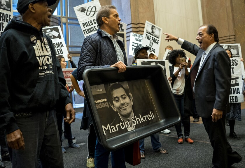 Not the most popular guy in the world: A protester carrying a cat litter box lined with an image of Turing Pharmaceuticals CEO Martin Shkreli appears at Turing's New York offices in October.