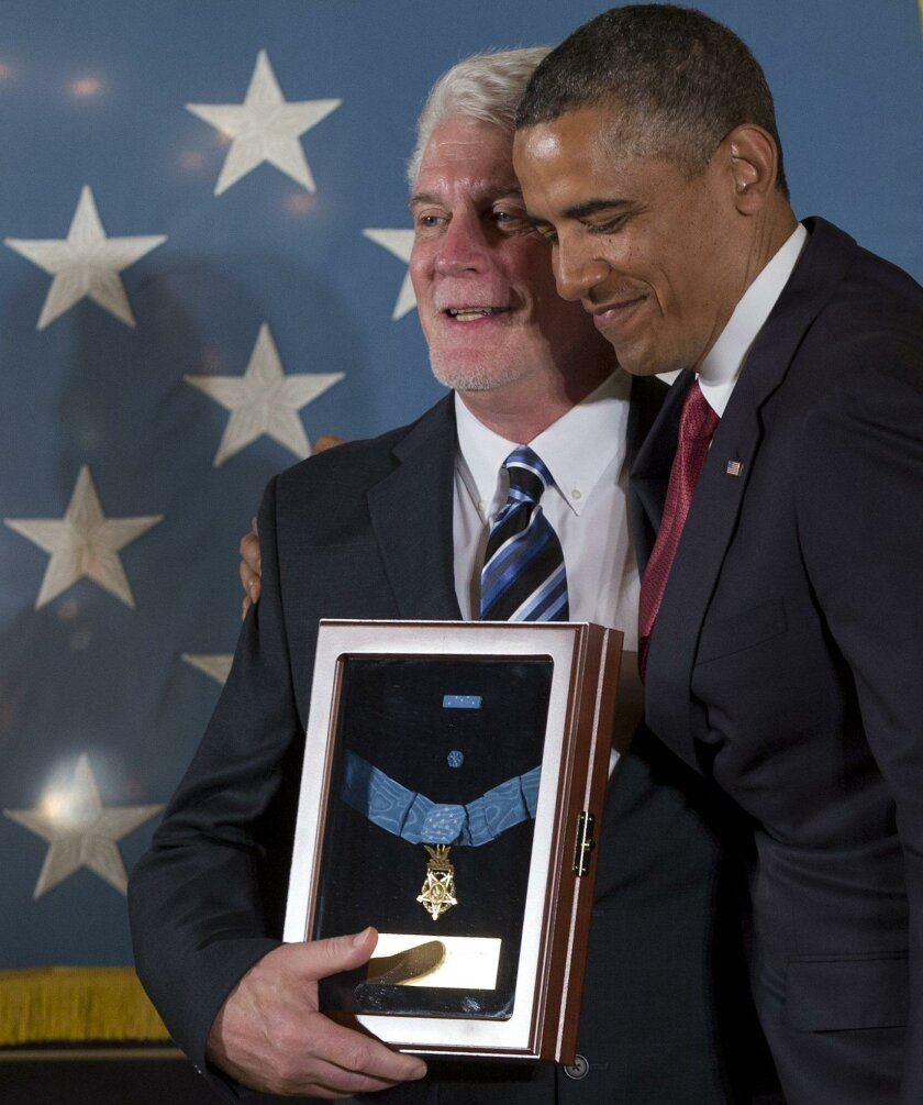 President Barack Obama stands with Ray Kapaun, nephew of Chaplain (Captain) Emil J. Kapaun, U.S. Army, as he awards the Medal of Honor posthumously to Chaplain Kapaun in the East Room of the White House in Washington, Thursday, April 11, 2013. Chaplain Kapaun will receive the Medal of Honor posthum