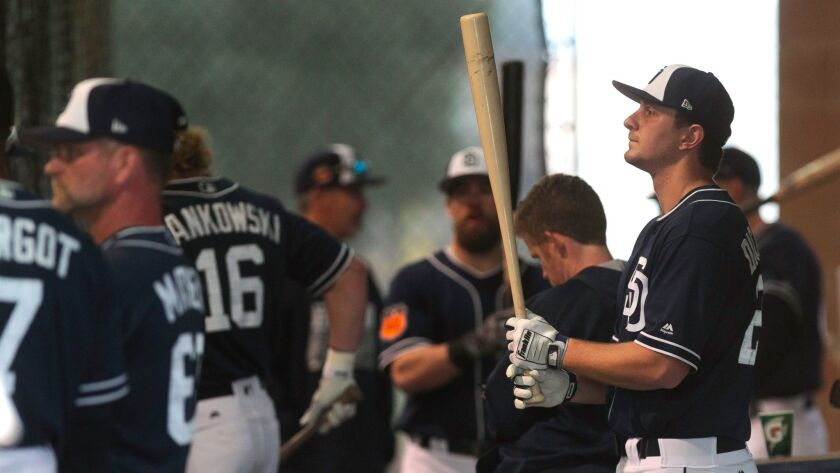 The Padres' Alex Dickerson holds up his bat as he and other players bat in the batting cages on the first day of Padres spring training with a full squad at the Peoria Sports Complex in Peoria, Ariz.