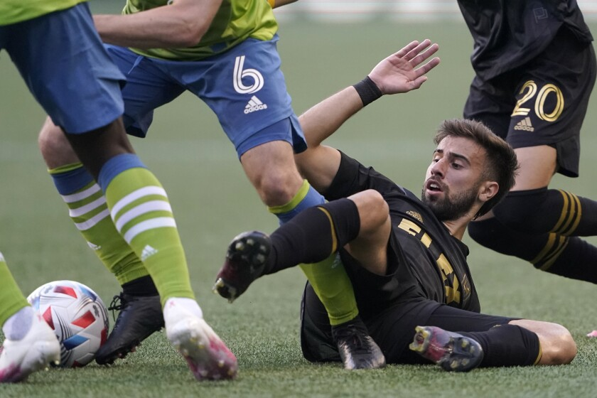 LAFC forward Diego Rossi is sprawled on the ground and battling to get to the ball during a match