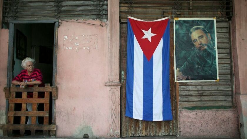 A Cuban flag and an image of Cuba's late President Fidel Castro hang on a wall as people head to Revolution Square for a massive tribute to Castro in Havana, Cuba, November 29, 2016.