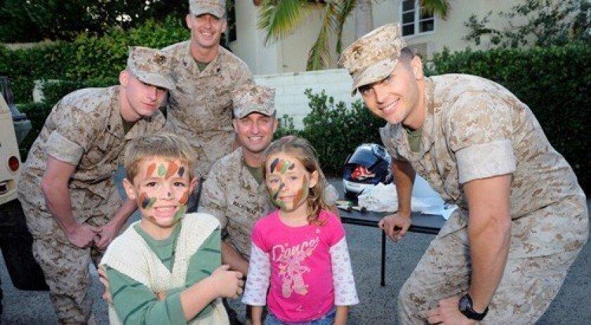 Paxton Scheibe and Liliana Neal, front, with U.S. Marine Corps members Blake Lucius, Nathan Burkhart, Adam Mackowiak, and Robert Regedanz (Photo: Jon Clark)
