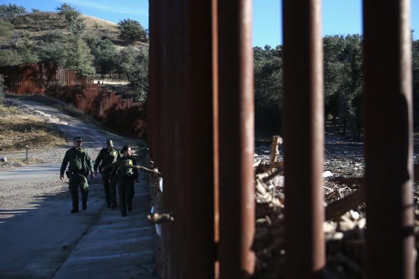 U.S. Border Patrol agents walk along the U.S.-Mexico border fence on Dec. 9, 2014, near Nogales, Ariz.