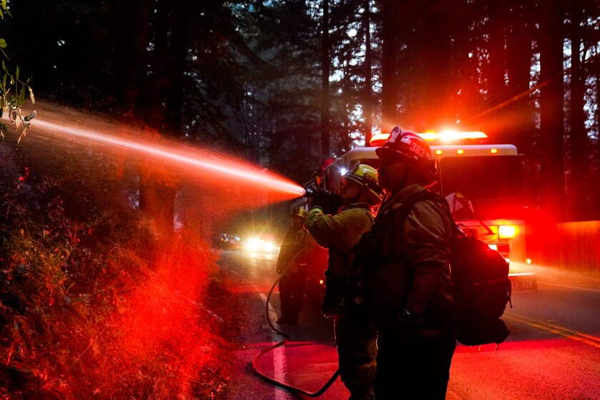 Firefighters tackle hotspots along Highway 9 during the CZU Lightning Complex fire Sunday in Boulder Creek, Calif.