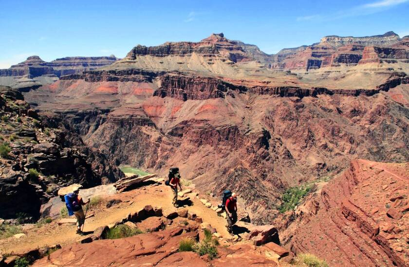 With the Grand Canyon as a magnificent backdrop, hikers make their way along the South Kaibab Trail. From here, there's a glimpse of the Colorado River below.