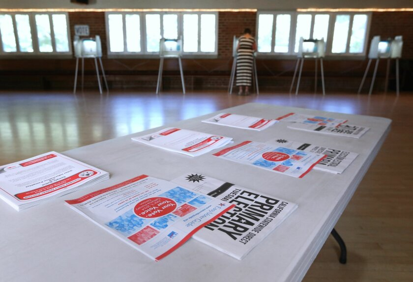 Voting pamphlets are displayed as a voter marks her ballot while voting in California's Primary Election in Sacramento,Calif., Tuesday, June 3, 2014. With no divisive ballot initiatives or high-profile races a low voter turnout is expected.(AP Photo/Rich Pedroncelli)