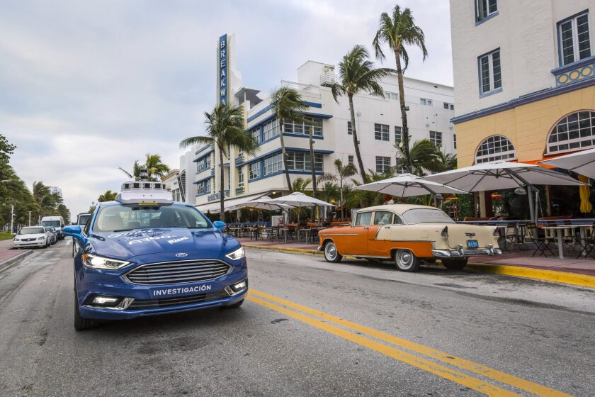 A self-driving Ford moves along a city street.