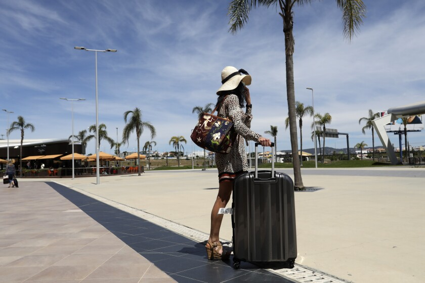 A woman in a dress and hat holds the handle of a rolling suitcase as she stands near a palm tree