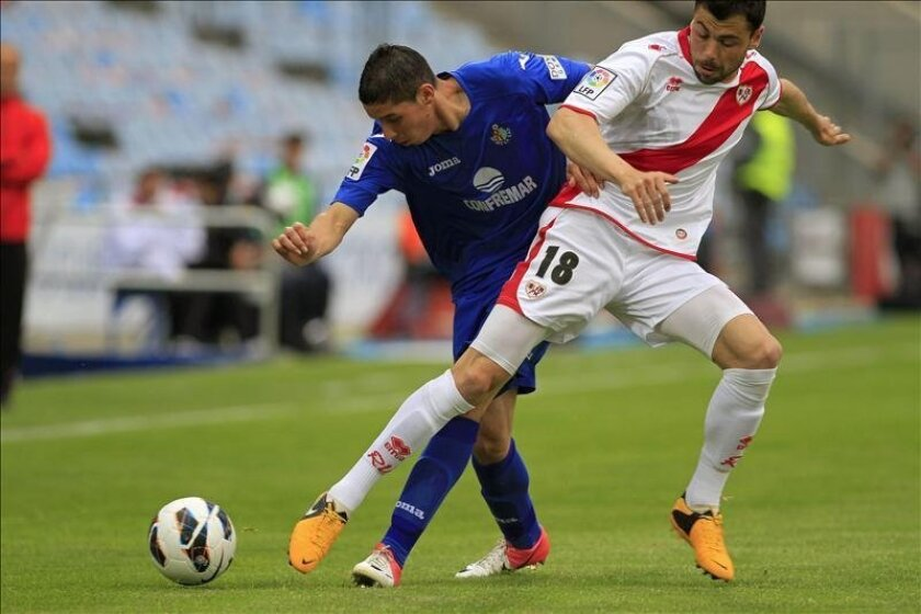 El portero del Getafe CF, Miguel Moyá (i), intenta evitar el avance del argentino Chori Domínguez, del Rayo Vallecano, durante el partido de Liga, correspondiente a la jornada trigésimo séptima en Primera División, que los dos equipos disputaron en el coliseum Alfonso Pérez, en Getafe. EFE