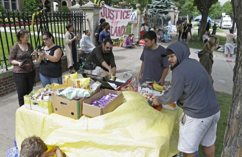 Manifestantes montan una mesa de comida afuera de la residencia del gobernador el viernes 8 de julio de 2016 en St. Paul, Minnesota, en donde las protestas contin˙an por la muerte de Philando Castile el miÈrcoles 6 de julio de 2016 en Falcon Heights. (AP Foto/Jim Mone)