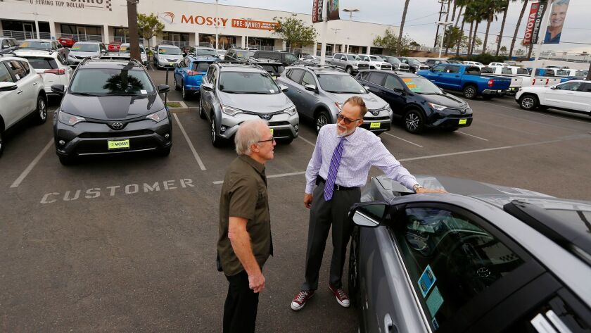 Salesman Rick Kitsmiller, right, shows off a Toyota Rav4 to customer Eric Jones at Mossy Toyota in Pacific Beach on Nov. 28, 2017. Light truck sales exceeded sales in cars in San Diego County and across California last year.