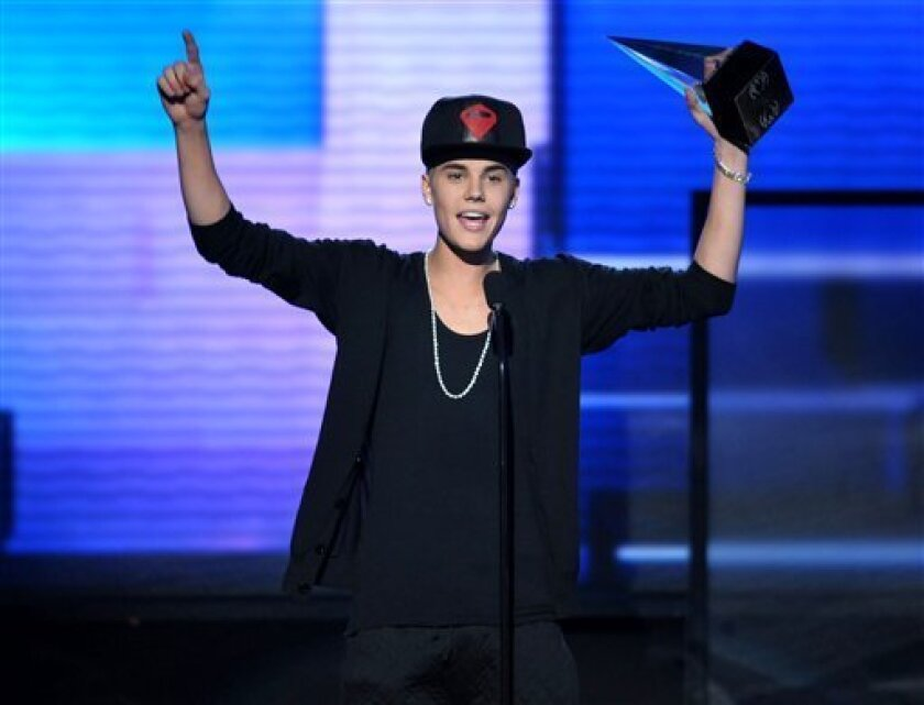 """FILE - In this Nov. 18, 2012 file photo, Justin Bieber accepts the award for favorite album - pop/rock for """"Believe"""" at the 40th Anniversary American Music Awards, in Los Angeles. A Los Angeles appellate panel wrote in a preliminary statement filed Monday, Jan. 28, 2013, that a 2010 California anti-paparazzi statute is constitutional. The law was used to charge a photographer for chasing Bieber last year, but a judge dismissed the anti-paparazzi counts in November 2012 because he said the law is overly broad and unconstitutional. (Photo by John Shearer/Invision/AP, File)"""