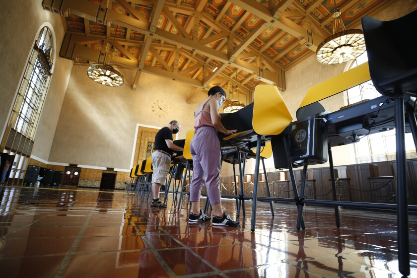 Two people vote at a long row of voting booths in a cavernous space.