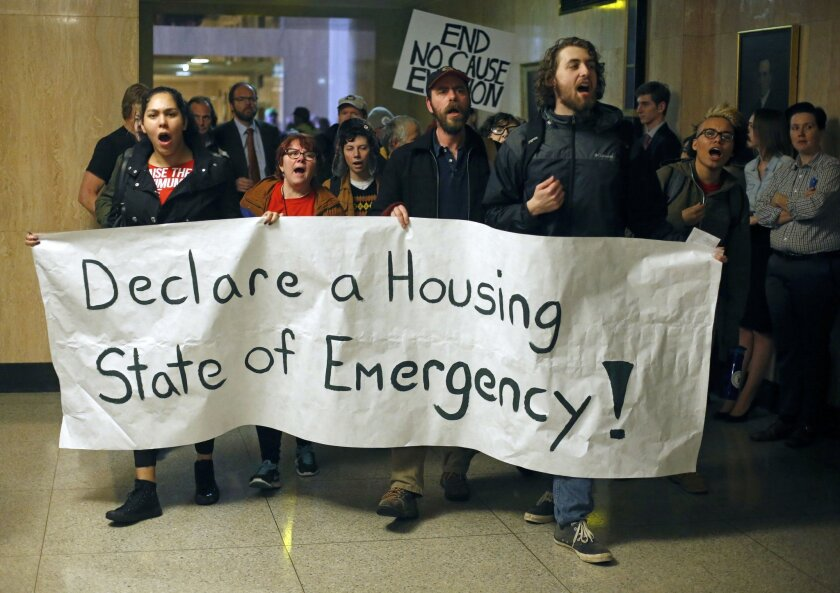 Protesters march through the Capitol Building, in Salem , Ore., on Thursday, Feb. 18, 2016. They were protesting for a higher minimum wage, local control of rent control laws, and an end to Oregon Department of Transportation sweeps of homeless camps. (AP Photo/Timothy J. Gonzalez)