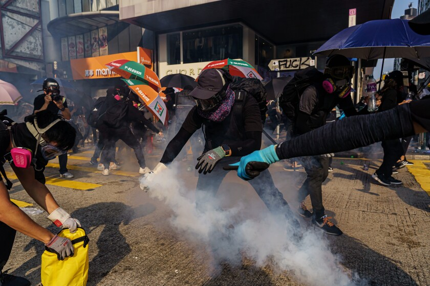 Protesters try to contain tear gas canisters in Hong Kong
