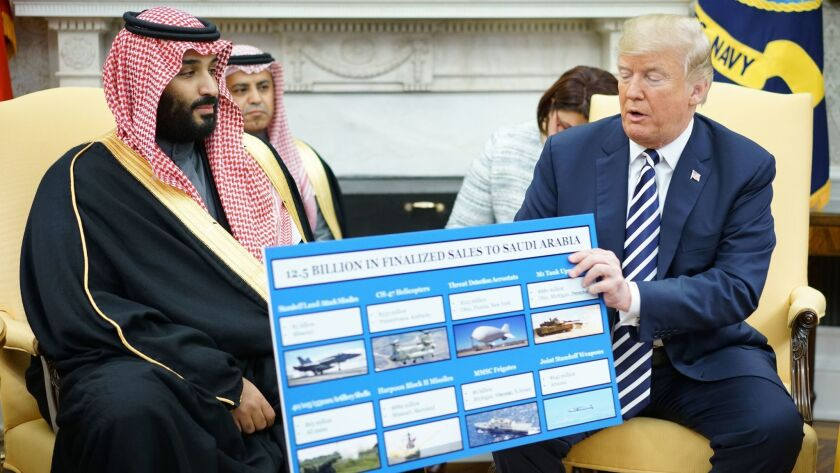 President Trump holds a defense sales chart during a meeting with Crown Prince Mohammed bin Salman of Saudi Arabia in the White House on March 20, 2018.