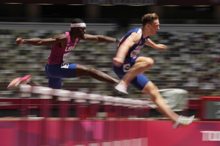 Norway's Karsten Warholm leads Rai Benjamin of the United States while leaping a hurdle.