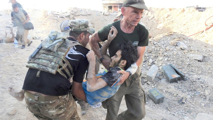 David Eubank, right, helps evacuate wounded Iraqi civilians from west Mosul.