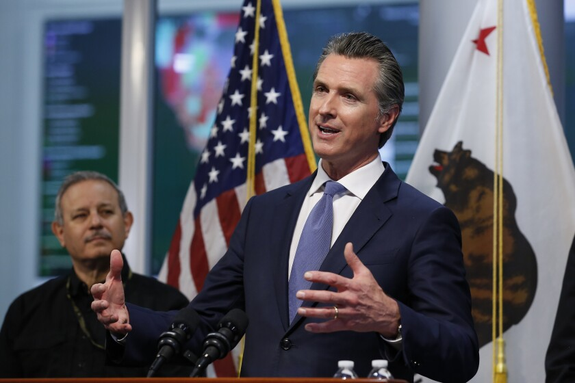 "FILE - California Gov. Gavin Newsom gives an update to the state's response to the coronavirus, at the Governor's Office of Emergency Services in Rancho Cordova Calif., Tuesday, March 17, 2020. At left is Mark Ghilarducci, director of the California Office of Emergency Services, OES. California is creating roving ""strike teams"" drawn from seven state agencies that will enforce state guidelines designed to slow the spread of the coronavirus, Gov. Gavin Newsom said Wednesday, July 1, 2020. The strike teams will be coordinated by the state's OES strike teams. (AP Photo/Rich Pedroncelli, Pool, File)"
