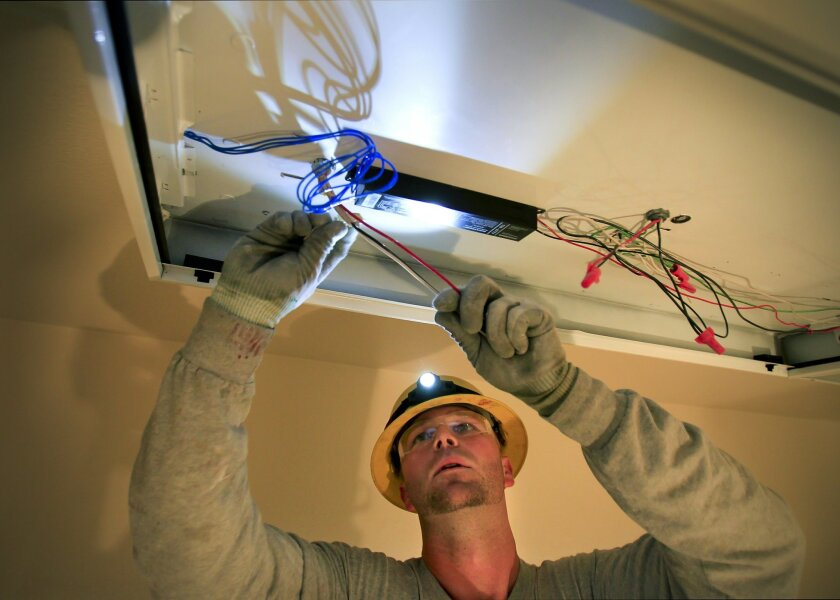 Christopher Sweeney, 30, is a trained electrician with Rowan Electric in Carlsbad. He is working on the lighting at at a commercial building in Carmel Mountain Ranch.