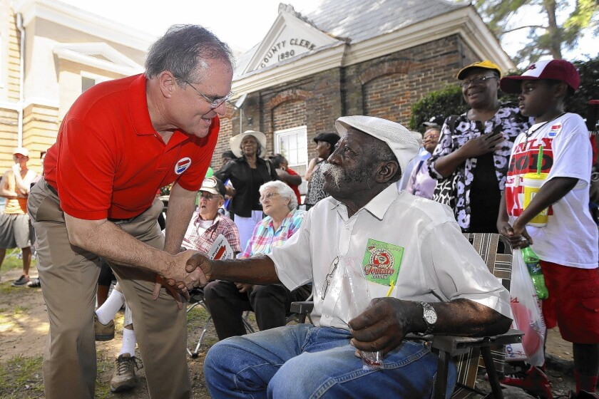 Sen. Mark Pryor (D-Ark.), left, greets Huey Furlough during a campaign visit in Warren, Ark., last month. Polls show the race between Pryor and tea party freshman Rep. Tom Cotton remains a tossup.