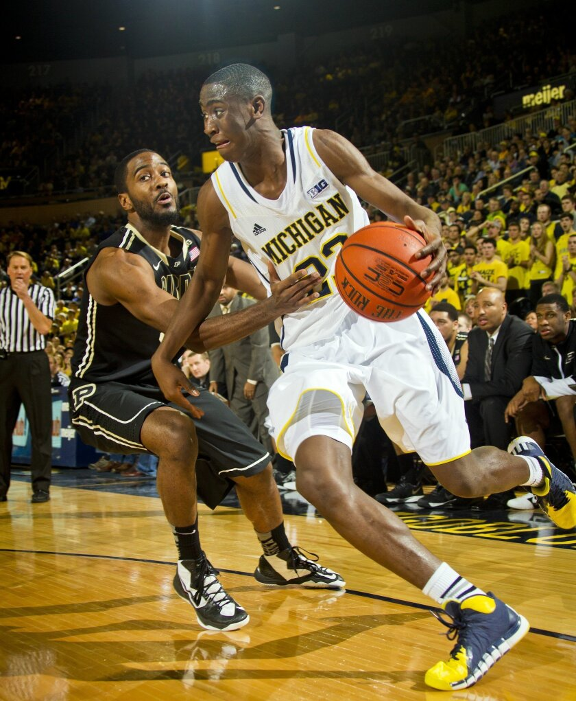 Purdue guard Rapheal Davis, left, defends Michigan guard Caris LeVert (23) in the first half of an NCAA college basketball game in Ann Arbor, Mich., Thursday, Jan. 30, 2014. (AP Photo/Tony Ding)