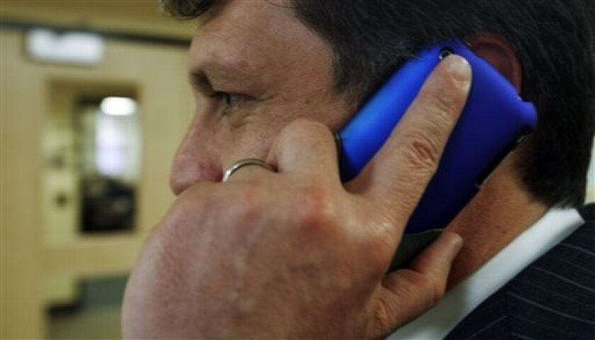 """FILE - In this March 2, 2010 file photo, an unidentified man talks on his cell phone in Augusta, Maine. When a mysterious, unauthorized fee appears on your cellphone bill, it's called """"cramming"""" and consumer advocates and regulators worry it's emerging as a significant problem as people increasingly ditch their landlines for wireless phones. (AP Photo/Pat Wellenbach, File)"""