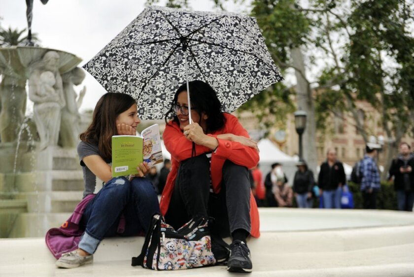 Scarlette Lutz and her mother, Chris, read a book during the 2016 L.A. Times Festival of Books at USC on Saturday.