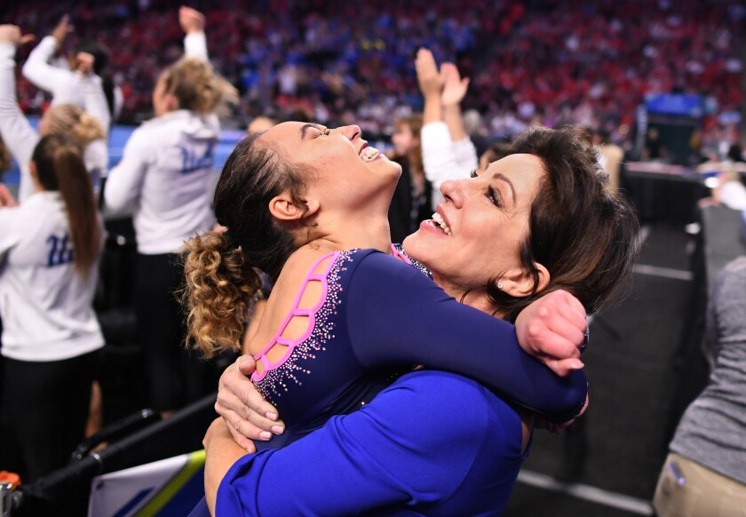 UCLA's Katelyn Ohashi jumps into the arms of coach Valorie Kondos Field.