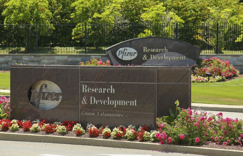 Pfizer signs are seen out front of the Pfizer Research & Development Laboratories Wednesday, July 22, 2020, in Groton, Conn. Pfizer on Tuesday, July 28, reported a 32% plunge in second-quarter profit, as the global coronavirus pandemic limited marketing of and new prescriptions for its medicines. Still, the biggest U.S. drugmaker posted a solid profit and nudged up parts of its 2020 financial forecast. (AP Photo/Stew Milne)