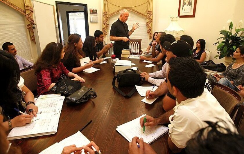 The Rev. Michael Bazzi, head of St. Peter Chaldean Catholic Cathedral, talks with new immigrants during a class in the church's rectory.