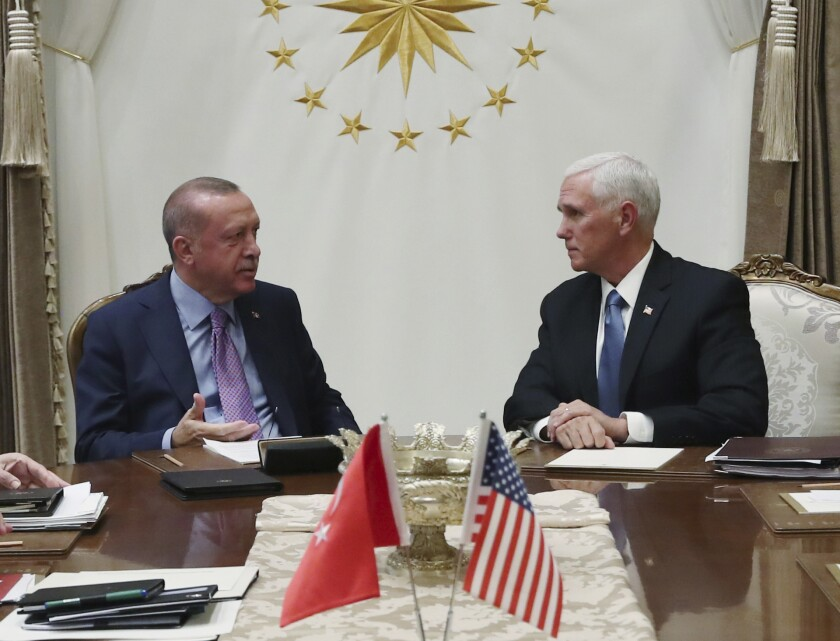 Turkey's President Recep Tayyip Erdogan, left, talks with U.S Vice President Mike Pence at the presidential palace in Ankara.