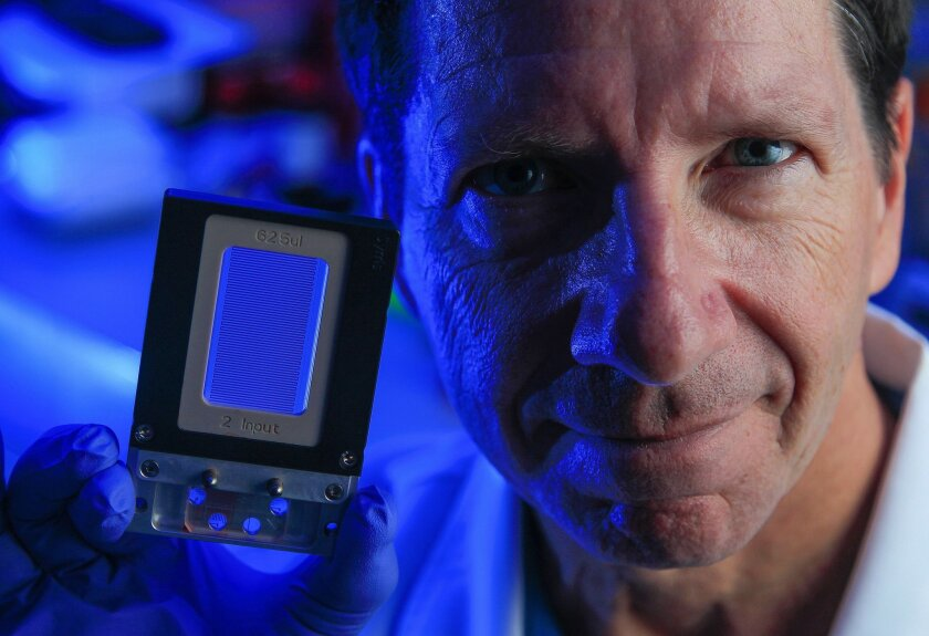 Jeff Allen, who is developing a cancer diagnostic chip similar to this one, poses for a picture in Nick Cosford's research lab at the Sanford Burnham Medical Research Institute. The chip Allen is developing would isolate cancer stem cells for diagnosis.