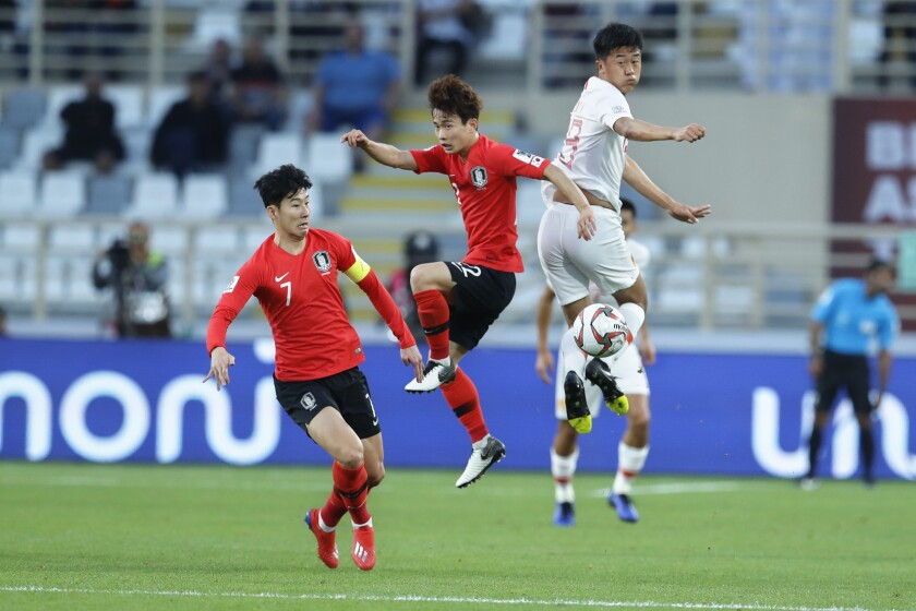 China's defender Liu Yang and South Korea's defender Kim Moon-Hwan jump for the ball.