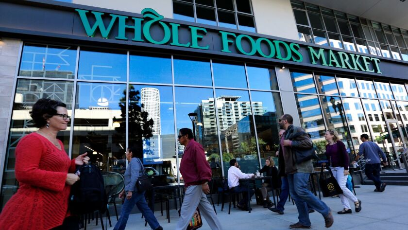 Pedestrians pass a Whole Foods Market in downtown Los Angeles in 2015. A recent report in the Financial Times said Albertsons owner Cerberus Capital Management was considering a takeover of the grocery chain.