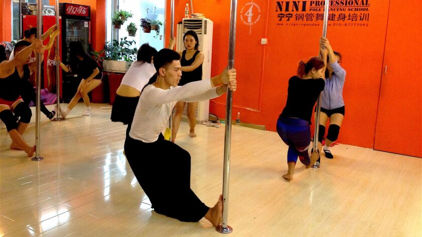 Hou Xing, 23, teaches a basic pole dancing technique course.