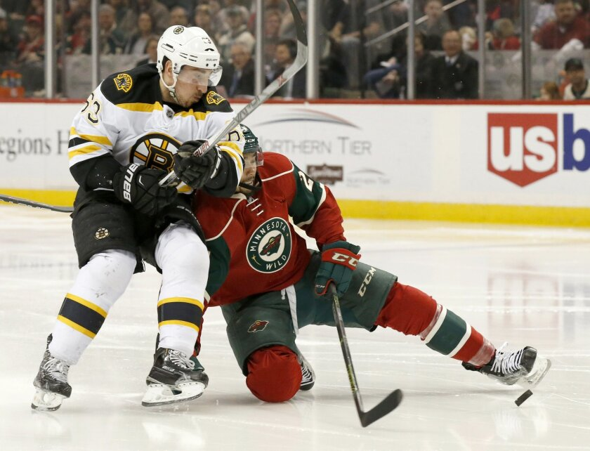 Boston Bruins left wing Brad Marchand (63) and Minnesota Wild defenseman Matt Dumba, right, battle for the puck during the second period of an NHL hockey game in St. Paul, Minn., Saturday, Feb. 13, 2016. (AP Photo/Ann Heisenfelt)