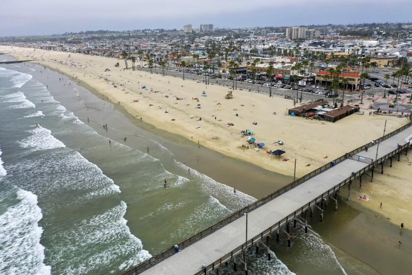 Beachgoers enjoy a partly sunny, warm day near the pier in Newport Beach on Tuesday.