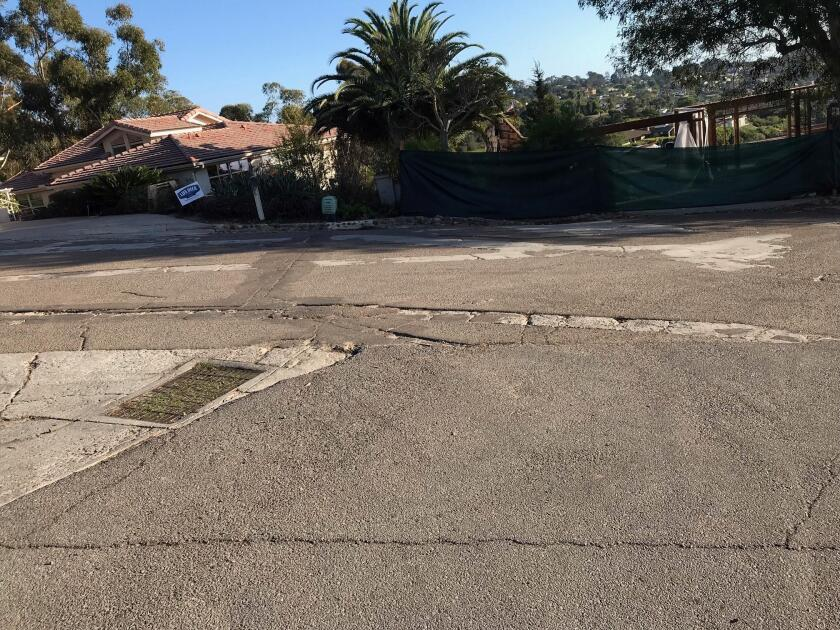 This picture of cracked roads, potholes and unevenpavement was taken at the intersection of Romero Drive and Brodiaea Way in La Jolla.