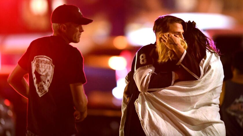 People comfort each other after a mass shooring at the Borderline Bar & Grill in Thousand Oaks late Wednesday night.