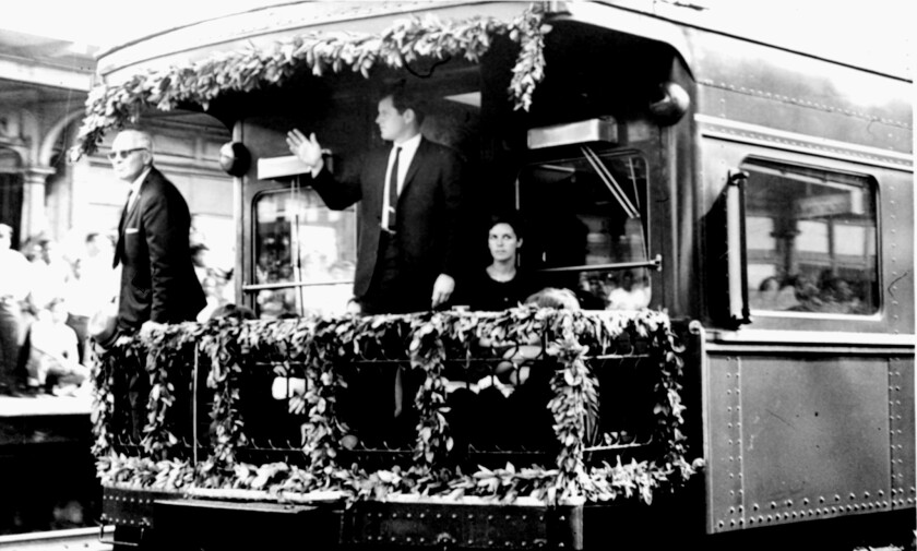 Sen. Edward M. Kennedy stands on the rear platform of the funeral train bearing the body of Sen. Robert F. Kennedy.