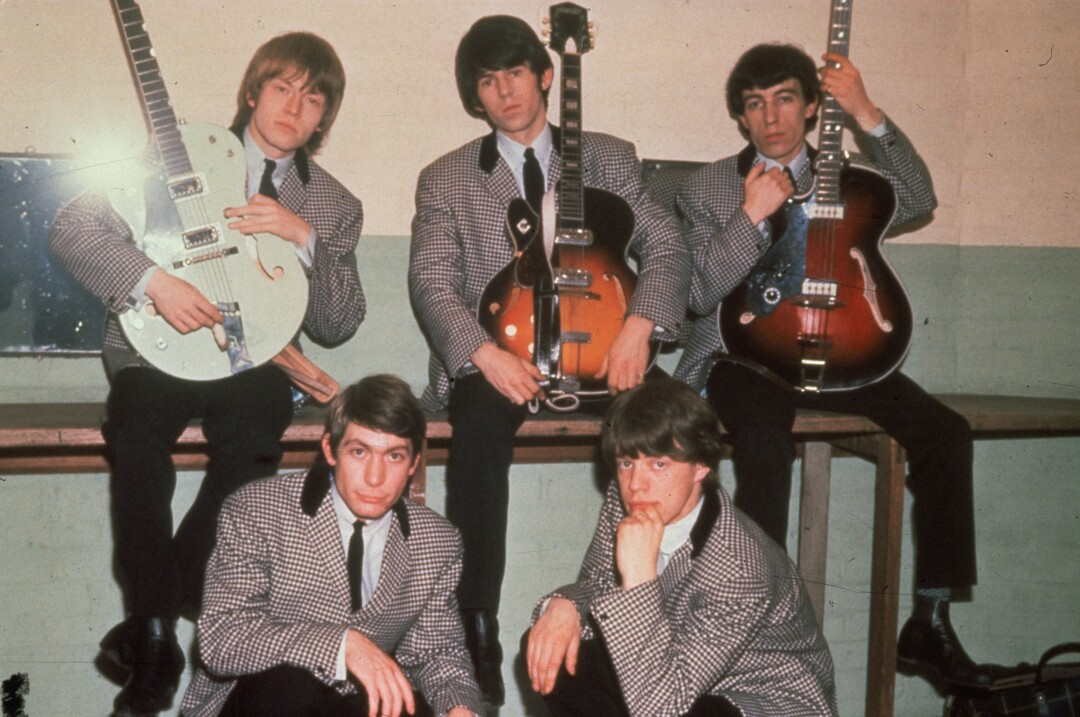 The Rolling Stones in 1964, wearing houndstooth suits, with three of them holding guitars.