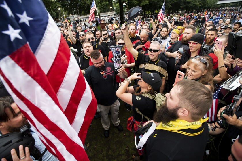 Members of right-wing groups plant a flag at Tom McCall Waterfront Park during a rally in Portland, Ore., in August 2019.