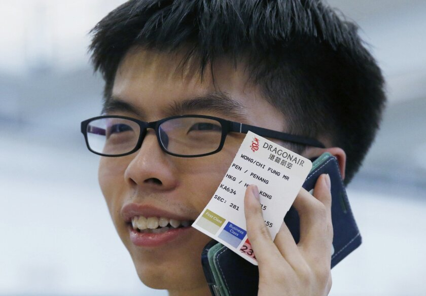 Hong Kong student leader Joshua Wong holding his flight boarding pass from Penang to Hong Kong talks on his mobile phone after arriving the Hong Kong airport Tuesday, May 26, 2015. The Hong Kong teen protest leader, who rose to prominence during last year's pro-democracy protests in the southern Ch